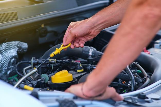 Крупным планом вид неузнаваемого человека, проверяющего уровень масла в своей машине