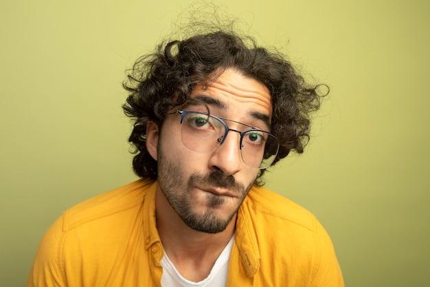 オリーブグリーンの壁に分離された正面の噛む唇を見ている眼鏡をかけている気になる若いハンサムな男の拡大図