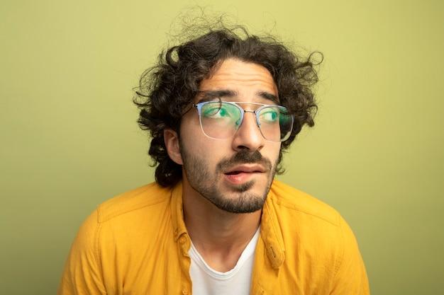 オリーブグリーンの壁に分離された唇を噛む側を見て眼鏡をかけて気になる若いハンサムな男の拡大図