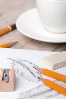 Крупным планом стол художника или дизайнера. чашка кофе, карандаши, точилка и ластик, лежащие на альбоме с рисованными перьями