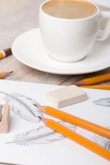Крупным планом стол художника или дизайнера. карандаши, резчик и ластик на альбоме с рисованными перьями