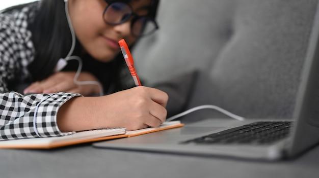 自宅のソファに横たわっている間、ラップトップコンピューターでオンラインコース中にアジアの女子学生のビューをクローズアップ。
