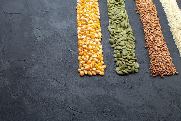 여유 공간이 있는 검은색 배경에 메밀 호박 씨앗 옥수수 쌀의 모듬 곡물의 보기를 닫습니다