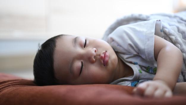 집에서 편안한 침대에서 잠자는 아기의 뷰를 닫습니다.