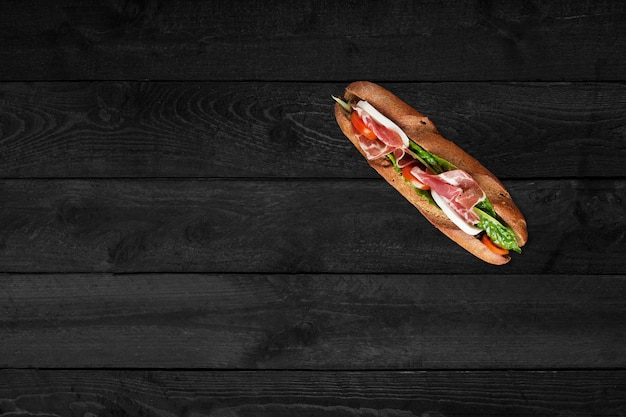 Крупным планом вид сэндвич с беконом, изолированные на черный деревянный стол.