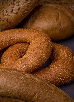 Взгляд крупного плана бубликов с отобранным хлебом багета и удара