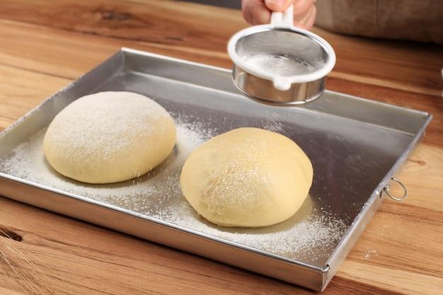 Крупным планом вид пекаря замешивания теста. домашний хлеб. руки готовят хлебное тесто на деревянном столе. приготовление традиционного домашнего хлеба. руки женщины замешивают свежее тесто для приготовления хлеба