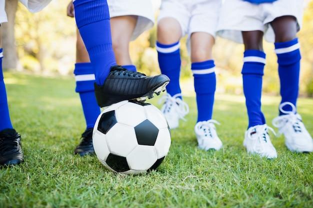 Крупным планом вид воздушного шара под футбольные бутсы с детьми, играющими