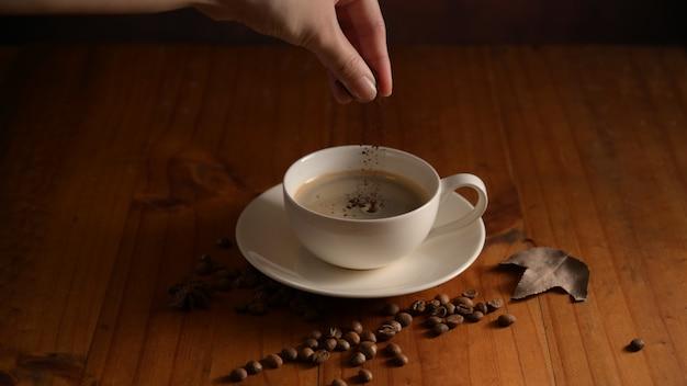コーヒー豆で飾られた木製のテーブルの上のカップにコーヒーパウダーを追加するバリスタの手のクローズアップ表示