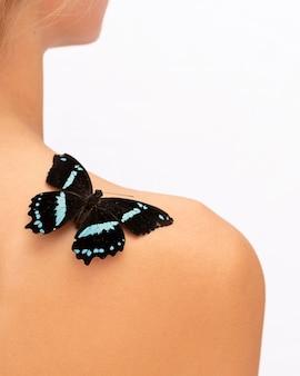 Крупным планом вид красивой бабочки на плече