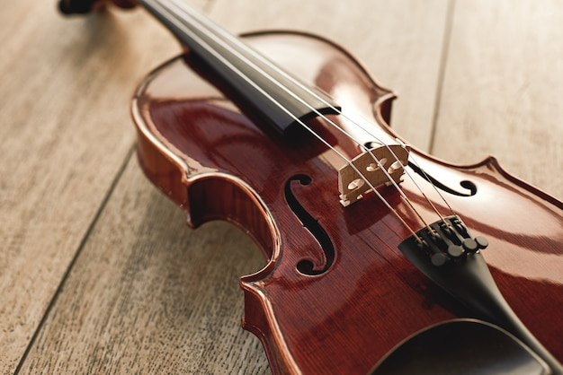 Крупным планом вид красивой классической скрипки, лежащей на деревянных фоне. музыкальные инструменты. музыкальное оборудование. музыкальный фон
