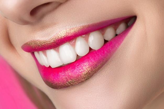 패션 메이크업으로 아름 다운 웃는 여자 입술의보기를 닫습니다. 스튜디오 촬영. 입술 화장품, 건강한 피부와 치아, 현대 메이크업 또는 행복한 여자 개념