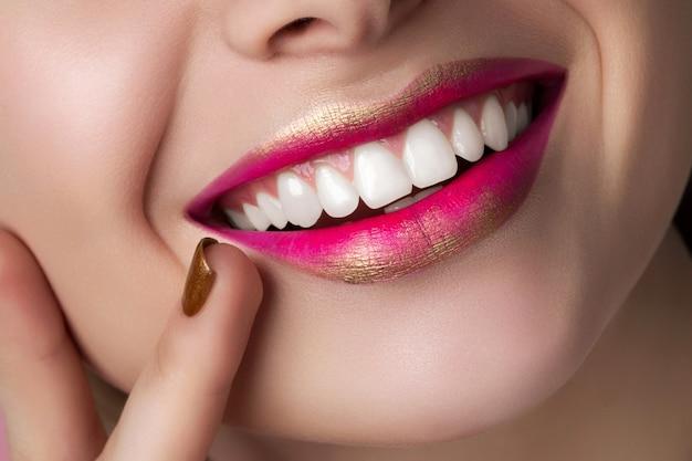 Крупным планом вид красивых улыбающихся губ женщины с модой составляет.