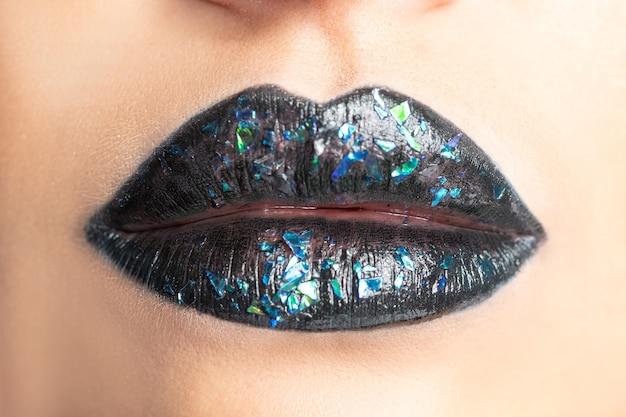 어두운 립스틱으로 아름 다운 여자 입술의보기를 닫습니다.