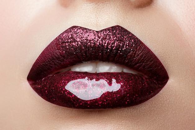 光沢のある濃い赤の口紅で美しい女性の唇のクローズアップビュー