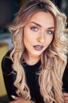 紫色のマットな口紅で美しい女性の唇のビューを閉じます。白い歯で口を開けてください。美容、ドラッグストアまたはファッションメイクのコンセプト。ビューティースタジオショット。情熱的なキス。