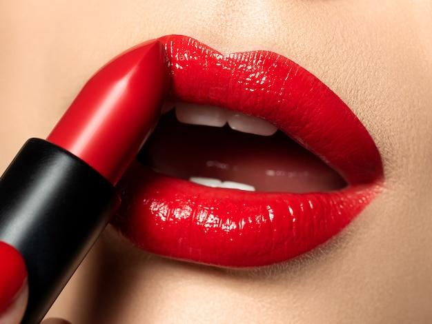 赤い口紅で美しい女性の唇のビューを閉じます。ファッションが構成します。美容、ドラッグストアまたはファッションメイクのコンセプト。