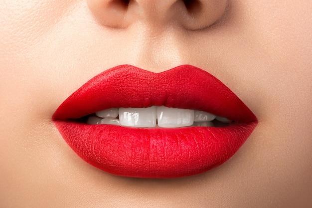빨간 매트 립스틱으로 아름다운 여자 입술의 뷰를 닫습니다
