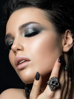Крупным планом вид красивой женщины, касаясь ее лица. идеальная кожа и вечерний макияж .. чувственность, страсть, модный молодежный макияж или концепция косметологии.