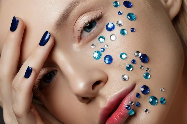 Крупным планом вид красивой женщины, касаясь ее лица. идеальная кожа и модный макияж. портрет красоты.