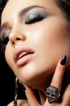 Крупным планом вид красивой женщины с вечерним макияжем, касающейся ее лица