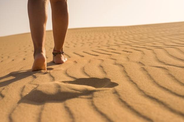 ビーチや砂丘で旅行やアウトドアレジャー活動を楽しんで砂漠の砂の上を歩く美しい女性の足のクローズアップビュー