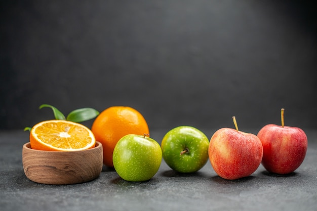 어두운 테이블에 신선한 오렌지와 녹색 사과와 혜택 과일 샐러드의 뷰를 닫습니다