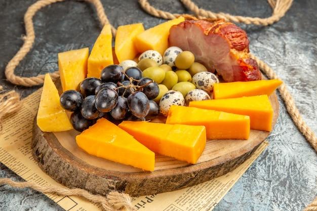 古い新聞の木製の茶色のトレイロープにさまざまな果物や食べ物と一緒に最高のスナックのクローズアップビュー