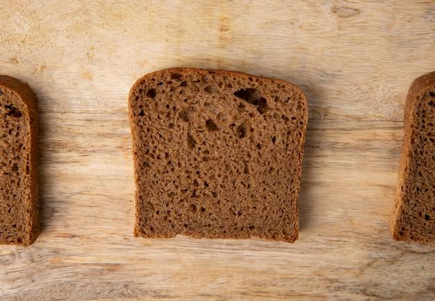 コピースペースを持つ木製の背景に黒のパンのスライスのクローズアップビュー