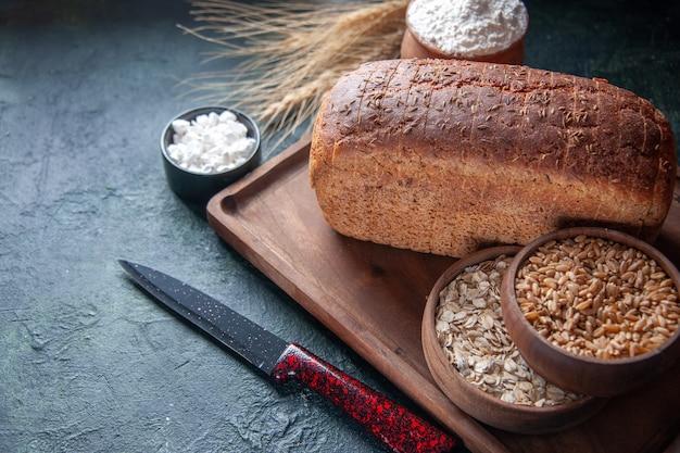 木の板のボウルに黒いパンのスライス小麦粉と混合色の苦しめられた背景の左側に生のオートミール小麦のナイフスパイクの拡大図