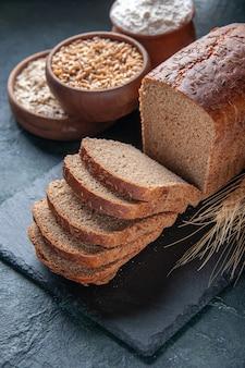 青い苦しめられた背景の上の暗い色のボード上の黒いパンのスライス小麦粉オートミールそばのクローズアップビュー