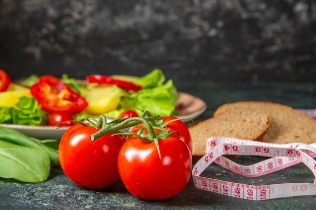 暗い色の表面に茎とメートルの緑の束が付いている黒いパンのスライスの新鮮なトマトの拡大図