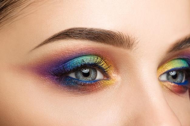 Крупным планом вид голубого женского глаза с красивым современным творческим макияжем