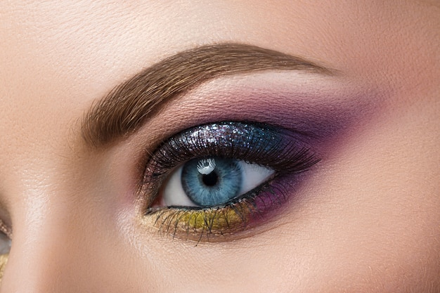 美しいモダンな創造的なメイクと青い女性の目のクローズアップビュー
