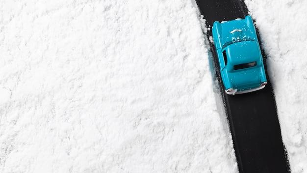Крупным планом вид голубой игрушечный автомобиль со снегом