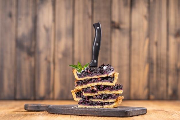 블루베리 파이 조각과 칼의 보기를 닫습니다. 수제 유기농 디저트. 호두를 넣은 블루베리 타르트. 복사 공간