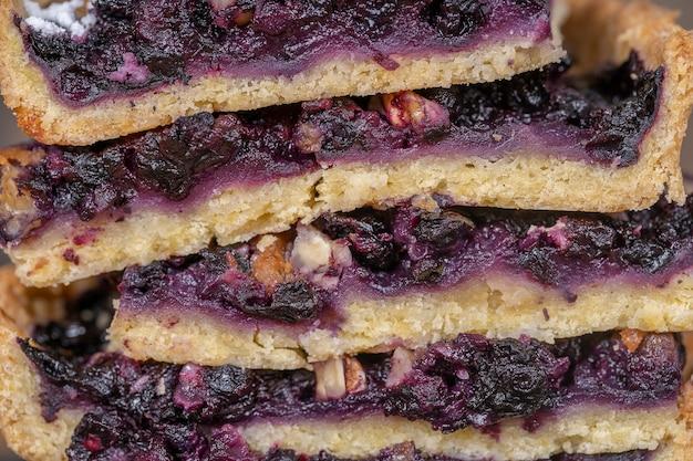 ブルーベリーパイの部分のクローズアップビュー。自家製オーガニックデザート。クルミとブルーベリーのタルト。ケーキの背景の断片