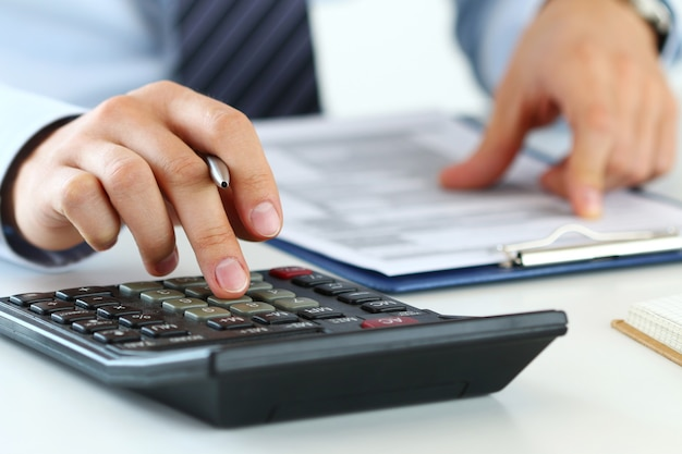 簿記係または財務検査官の手がレポートを作成し、残高を計算またはチェックしている様子をクローズアップします。住宅金融、投資、経済、お金の節約または保険の概念
