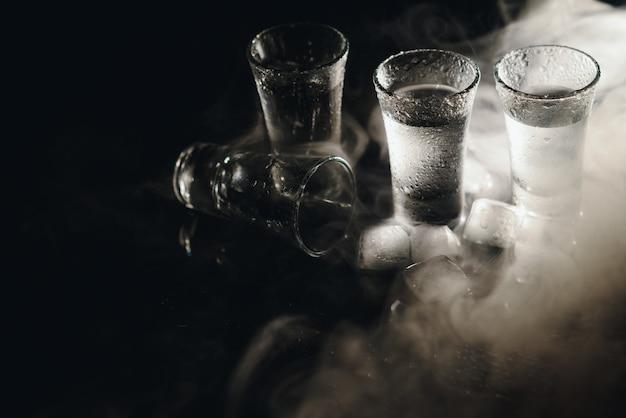 黒で隔離の立っているウォッカのボトルとグラスの拡大図