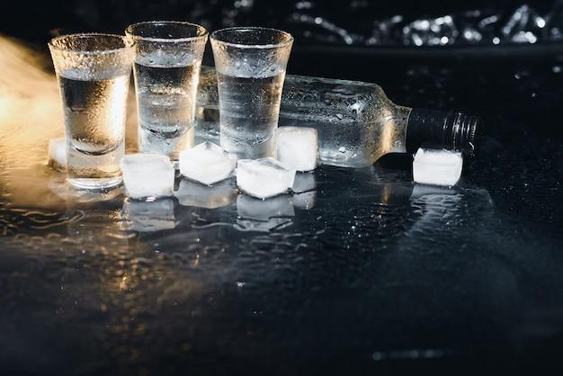 黒の氷の上に立っているグラスとウォッカのボトルの拡大図
