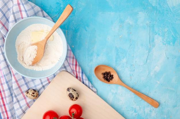 小麦粉のボウルとコピースペースと青の背景に卵と黒胡椒のクローズアップビュー
