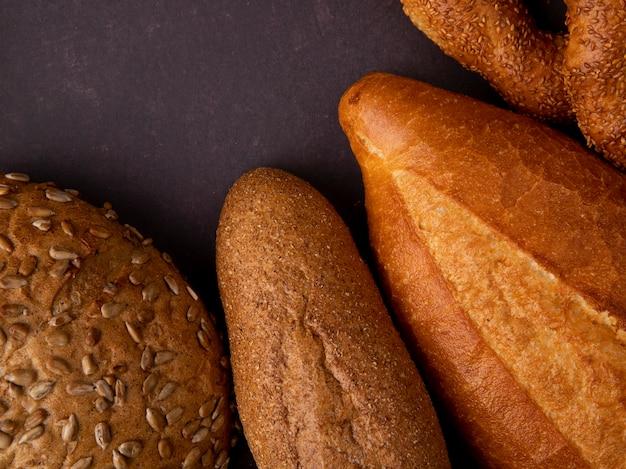 복사 공간 적갈색 배경에 옥수수 바게트 베이글로 빵의 근접 촬영보기