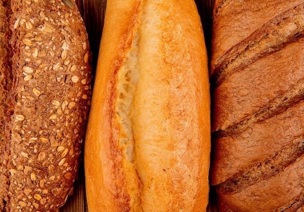 Взгляд конца-вверх хлебов как въетнамский и черный отобранный багет и черный хлеб на деревянной поверхности