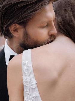 신부의 뒷모습, 신랑이 여자를 껴안고 그녀의 목에 키스하는 모습을 클로즈업