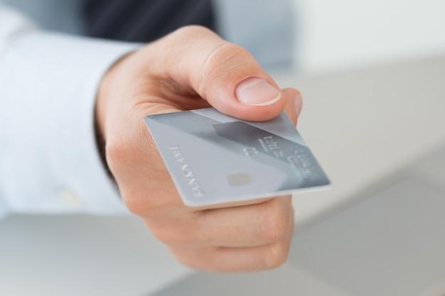 クレジットカードを持っているビジネスマンの手のクローズアップ。オンライン決済、eコマース、インターネットバンキング、ショッピング、配達、詐欺防止、または金融セキュリティの概念。