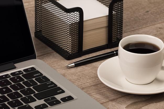 ビジネスマンの職場の拡大図。一杯のコーヒー、ラップトップ、ノートブック、ペン。ビジネス、教育またはブログの概念。