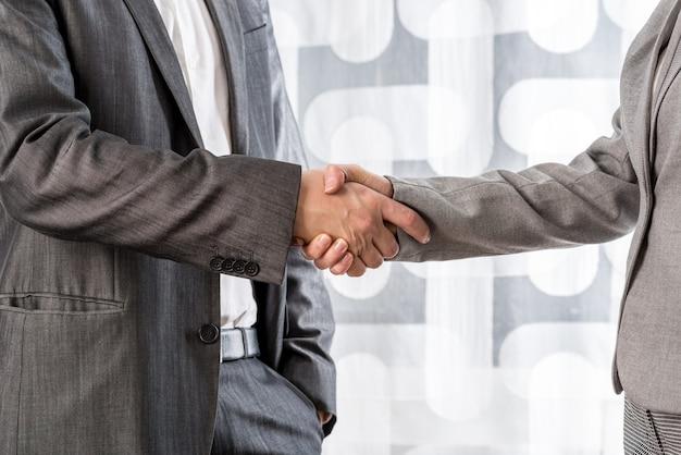 Крупным планом вид бизнесмена и бизнес-леди, пожимая руки