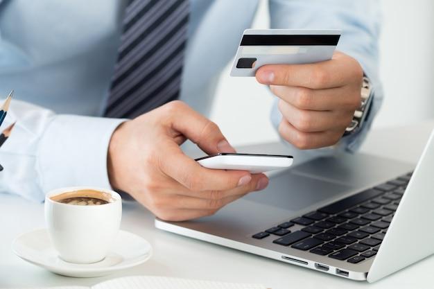 クレジットカードを保持し、携帯電話を使用してオンライン購入を行うビジネスマンの手をクローズアップします。ショッピング、消費主義、配達、金融セキュリティ、詐欺防止またはインターネットバンキングの概念。