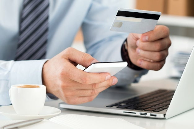 신용 카드를 들고 휴대 전화를 사용하여 온라인 구매를하는 사업가 손의 뷰를 닫습니다.