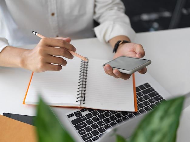 Крупным планом бизнесмен, использующий смартфон, работая над своим планом в своем рабочем пространстве